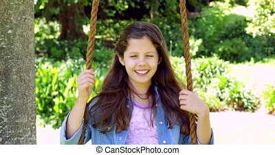 Smiling little girl sitting on a swing