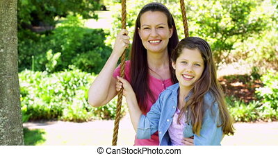 Mother and daughter sitting on a swing