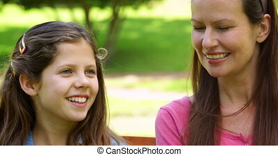 Mother and daughter chatting on a park bench on a sunny day...