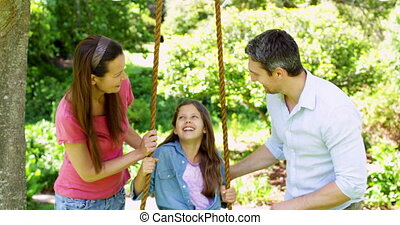 Parents pushing their daughter on a swing in the park on a...