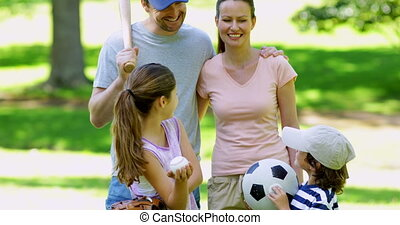 Sporty family smiling at camera in the park on a sunny day