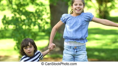Cute siblings jumping up and down on a sunny day