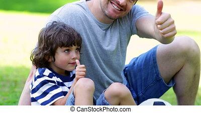 Father sitting with little son in the park