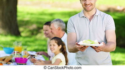 Father offering plate of food to camera at family barbecue...