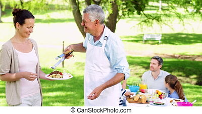 Grandfather serving burgers at family gathering -...