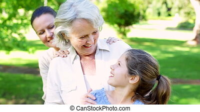 Three generations of women smiling at camera in the park on...