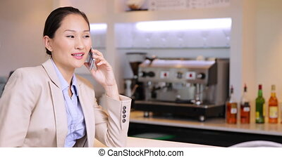 Asian businesswoman chatting on her phone at the local bar