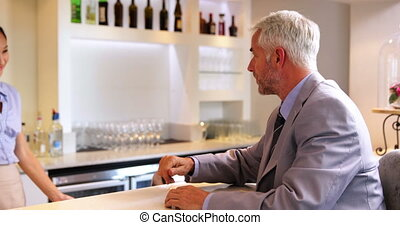 Businessman ordering a drink from barmaid at the local bar