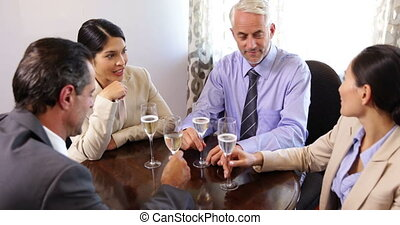 Business associates drinking wine after work at the local...