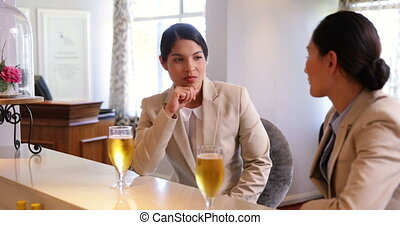 Businesswomen having a glass of beer after work at the local...