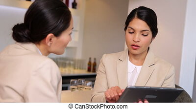 Businesswomen looking at tablet at the local bar