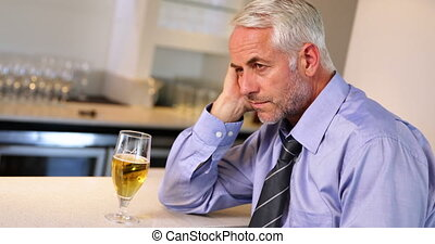 Lonely businessman drinking a beer after work at the local...