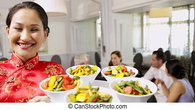 Smiling waitress presenting tray with bowls of vegetables at...