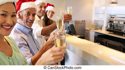 Group of friends celebrating christmas with champagne at the...