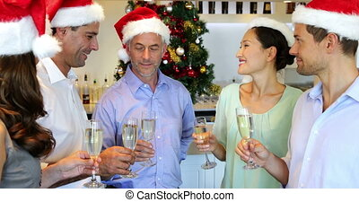 Happy friends celebrating christmas together with champagne...