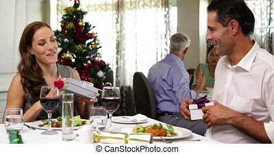 Happy couple having a christmas meal together and exchanging...