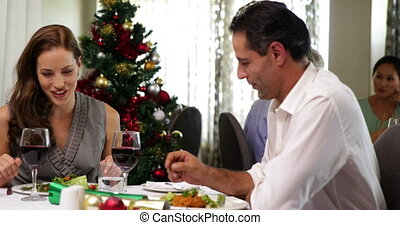 Happy couple having a christmas meal together at a...