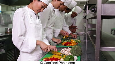 Team of chefs slicing vegetables in a commercial kitchen