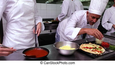 Happy chef preparing a pizza in a commercial kitchen