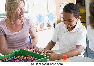 A schoolboy and his teacher in an art class
