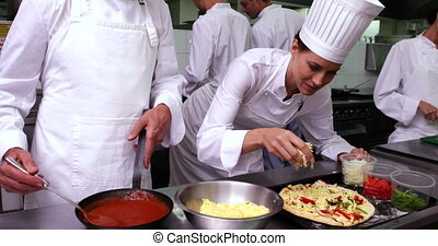 Happy pretty chef preparing a pizza in a commercial kitchen