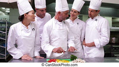 Team of chefs watching head chef slicing vegetables in a...