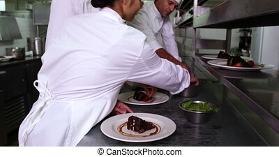 Row of chefs garnishing dessert in a commercial kitchen