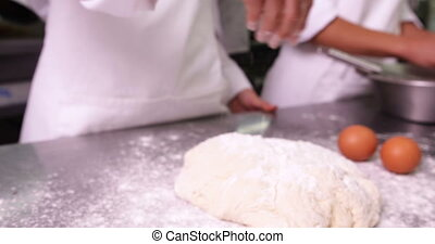 Chefs preparing dough at counter in a commercial kitchen