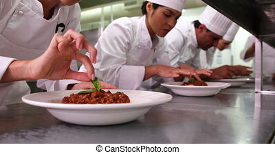 Row of chefs garnishing spaghetti dishes in a commercial...