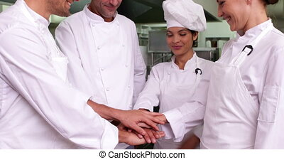 Team of chefs putting hands togethe