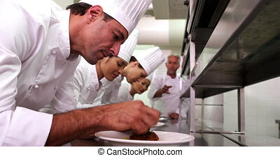 Head chef supervising his team garnishing plates in a...