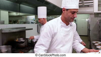 Smiling handsome chef showing two dishes to camera in a...