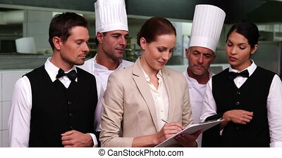 Serious restaurant staff with manager looking at camera in a...