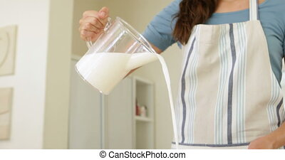 Woman pouring milk into bowl of flour at home in the kitchen