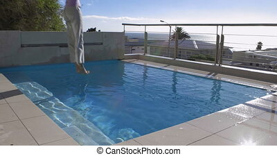 Woman jumping into pool fully cloth - at home on the balcony