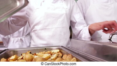 Row of chefs lifting lid off serving trays in a commercial...