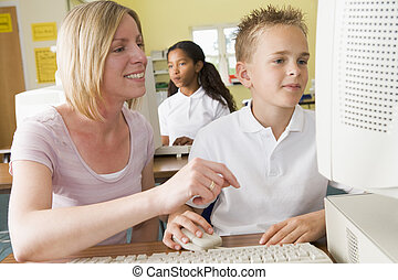 Teacher and schoolboy studying in front of a school computer