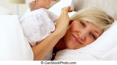Woman covering her ears as partner snores - Woman covering...