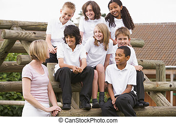 School children sitting on benches outside with their...