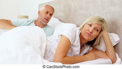 Couple having an argument in bed at home in bedroom