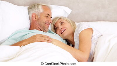Couple chatting in bed and cuddling at home in bedroom