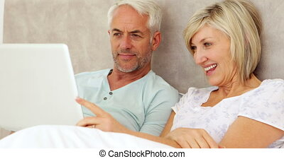 Happy couple chatting and using laptop in bed at home in...