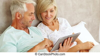Couple chatting and using tablet in bed at home in bedroom