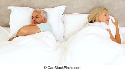 Couple not speaking in bed at home in bedroom