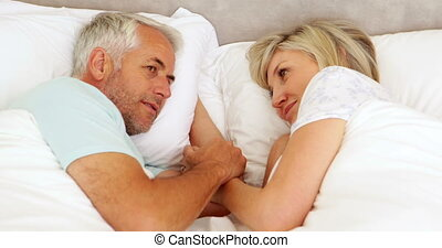 Happy couple chatting and holding hands in bed at home in...
