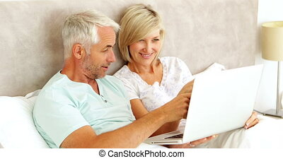 Couple chatting and using laptop in bed at home in bedroom