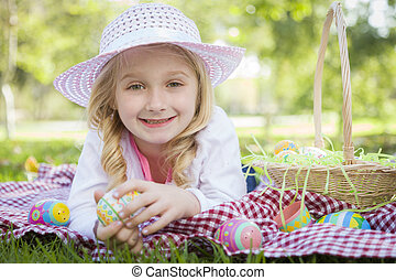 Cute Young Girl Wearing Hat Enjoys Her Easter Eggs