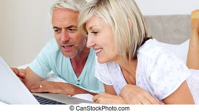 Happy couple lying on bed using laptop together at home in...