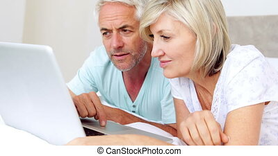 Happy couple lying on bed using laptop at home in bedroom