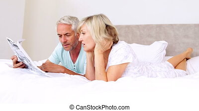 Couple lying on bed reading newspaper together at home in...